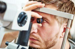 Mann lässt sich beim Optiker seine Kontaktlinsen anpassen