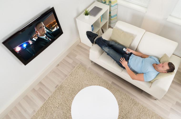 Mann, der auf einer Couch liegt und auf einen Fernseher schaut