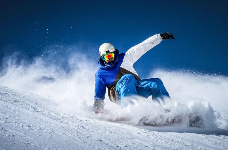 Mann fährt Snowboard